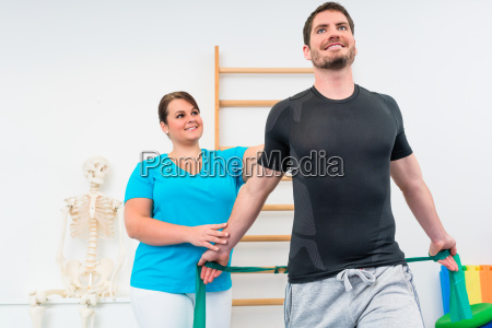young man working out with physiotherapist