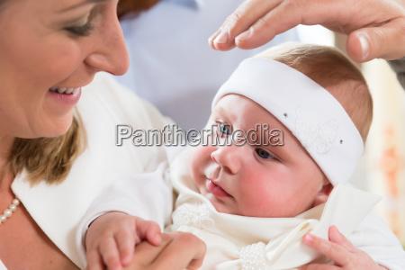 mor baby og praester holder ved