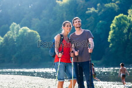 couple hiking at river in summer