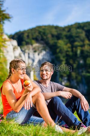 man and woman having break hiking
