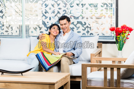asian couple buying sofa in furniture