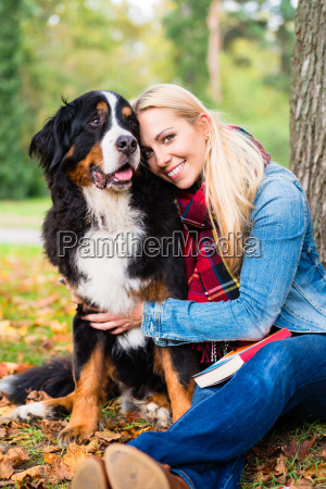 woman cuddling with dog outside in
