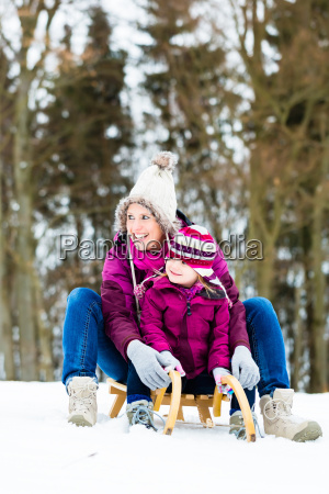 woman and daughter on sled in