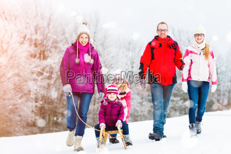 family having winter walk in snow