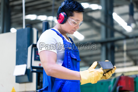 worker in industrial factory checking work