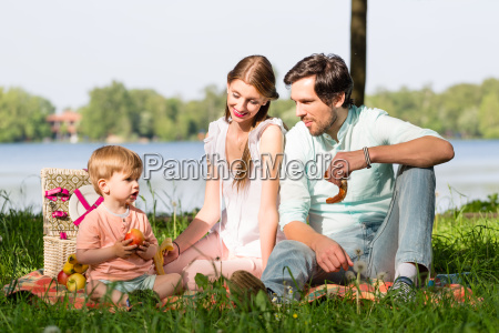 family having picnic at lake sitting