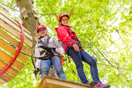sisters climbing in high rope course