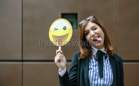 businesswoman holding emoji smiling with tongue