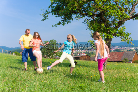 family playing soccer on meadow in