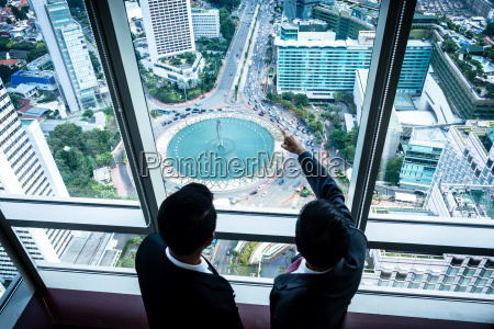 two asian businesspeople looking down to