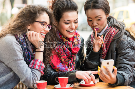 women in cafe showing pictures on