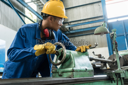 worker checking quality behind an industrial
