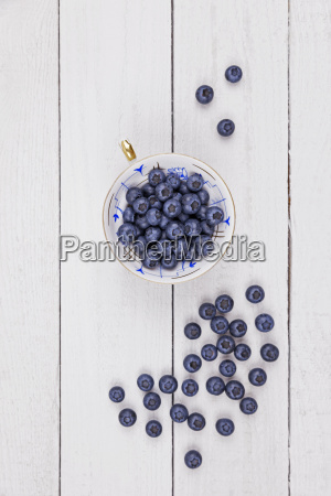 collectors cup of blueberries on wood