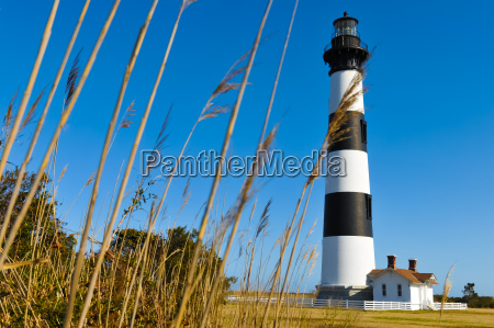 striped lighthouse by the grass