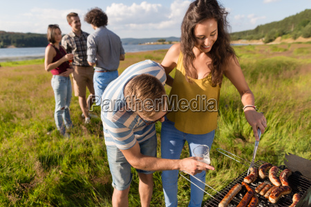 man and woman grilling bratwurst on
