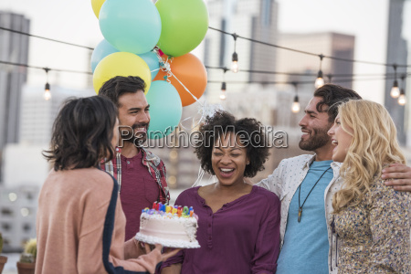 friends celebrating birthday party on rooftop