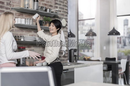 two female friends in modern kitchen