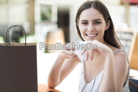 smiling woman with shopping bag enjoying