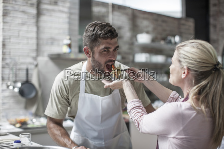 couple cooking together and tasting food