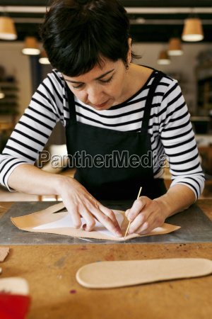 shoemaker working on template in her