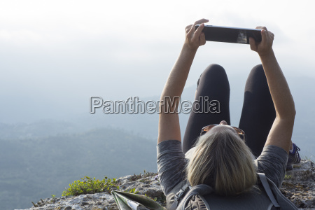 mature woman hiker reclines on cliff