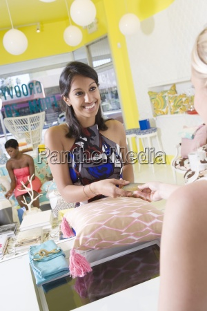 woman buying cushion at store