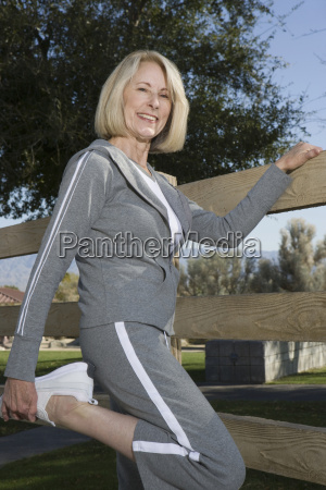 mature woman stretches leg in warm