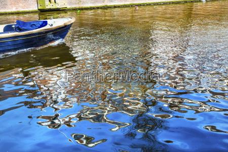 blue boat reflection singel canal amsterdam