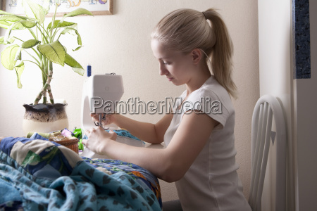 woman making patchwork at sewing machine