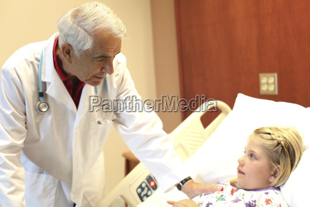 senior pediatrician examining girl in clinic