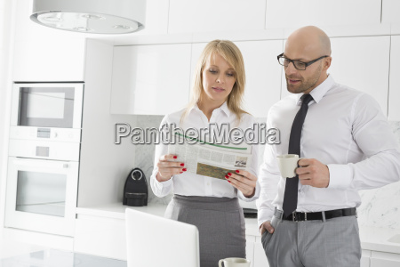 mid adult business couple reading newspaper