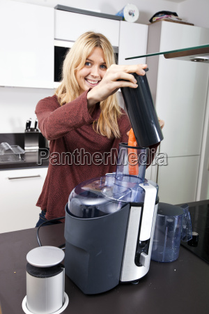portrait of woman using juicer for