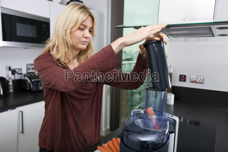 young blond woman juicing carrots in