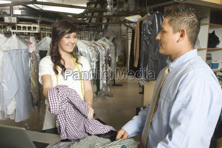 owner showing dry cleaned clothes to