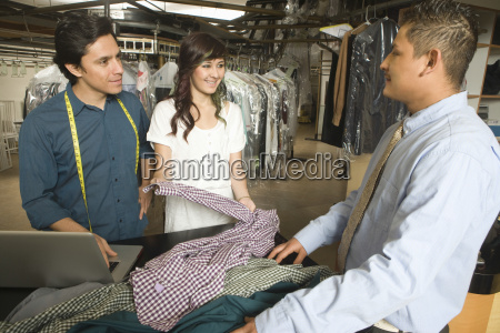 owners showing dry cleaned clothes to