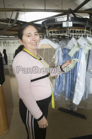owner with receipt standing by clothes