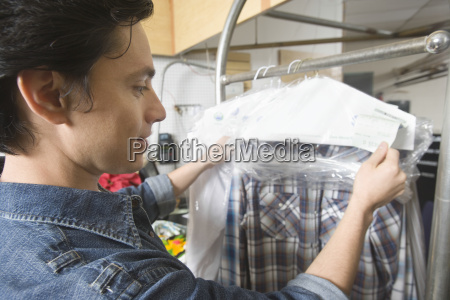 owner checking clothes on rail in