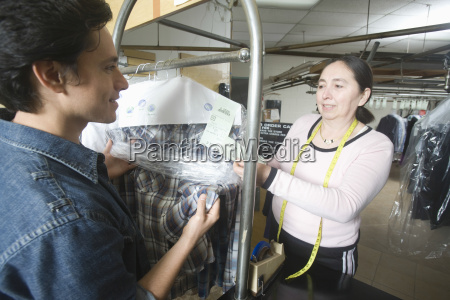 customer checking dry cleaned clothes with