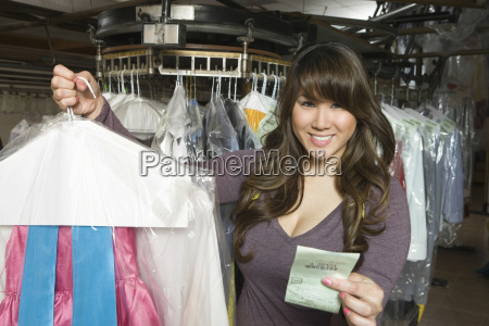 woman holding dry cleaned clothes and
