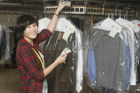 owner holding receipt by clothes rail