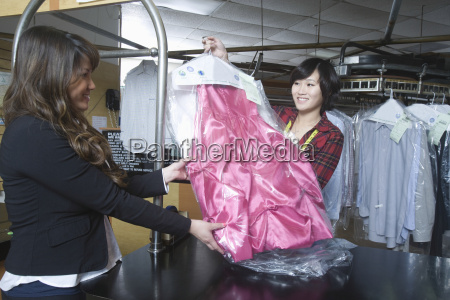 customer collecting clean dress from owner