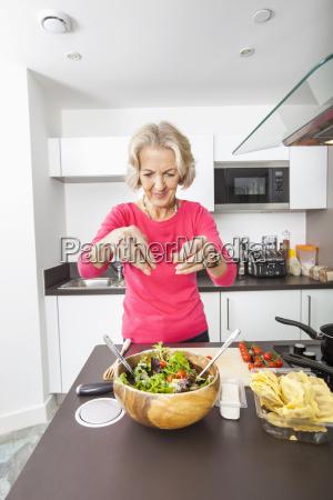 senior woman preparing salad at kitchen