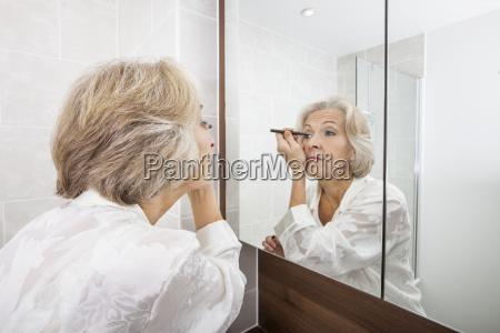 senior woman applying eyeliner while looking