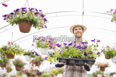 happy gardener holding flower pots in