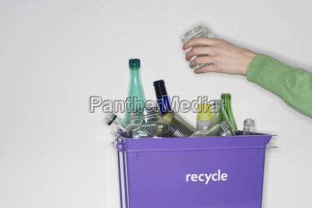 person putting jar into recycling container