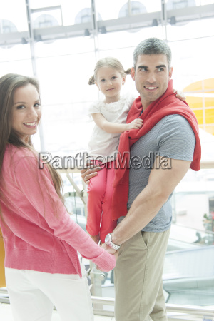 father holding young daughter up at
