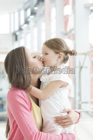 mother and daughter hug and kiss