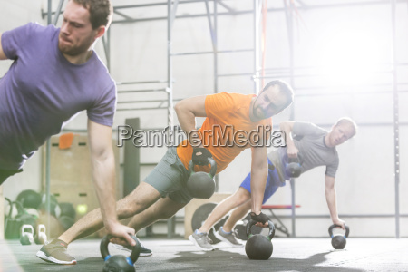 men exercising with kettlebells in crossfit