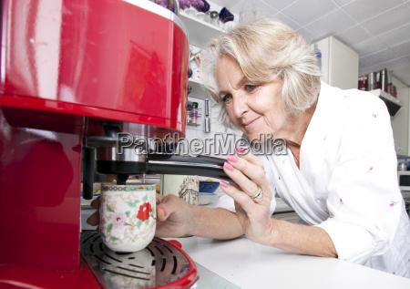 senior woman dispensing coffee from machine