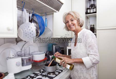 portrait of senior woman adding olive